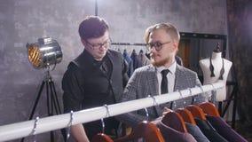 Het winkelen concept De verkoper helpt een jonge mens om een kostuum in de opslag te kiezen stock video