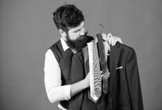Het winkelen concept Dienst van de winkel de hulp of persoonlijke stilist Stilistraad De aanpassing van stropdas met uitrusting G stock afbeeldingen