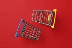 Het winkelen concept Twee boodschappenwagentjes op een rode achtergrond royalty-vrije stock fotografie