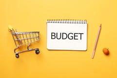 Het winkelen concept Het concept van de begroting Boodschappenwagentje, leeg document notitieboekje met pen op een gele achtergro stock foto's