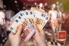 Het winkelen conceptie, vrouwelijke handen met euro bankbiljetten stock fotografie