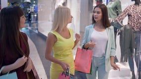 Het winkelen dag, gaan de gelukkige meisjes in modieuze heldere kleding voorbij vensterswinkel en bespreken manier in seizoen van stock footage