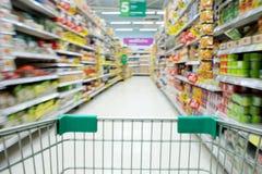 Het winkelen in de mening van het supermarktboodschappenwagentje met motieonduidelijk beeld Royalty-vrije Stock Afbeelding