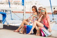 Het winkelen dichtbij overzees drie gelukkige vrienden Royalty-vrije Stock Foto