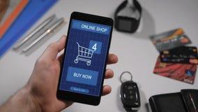 Het winkelen in een online opslag op uw smartphone De man heeft reeds de goederen gekozen, zijn zij in de virtuele mand stock video