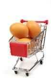 Het winkelen karretje en verse eieren Stock Foto's