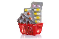 Het winkelen karretje met pillen en geneeskunde op wit wordt geïsoleerd dat Stock Foto's