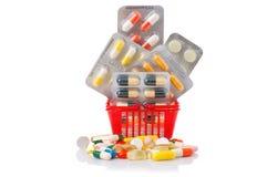 Het winkelen karretje met pillen en geneeskunde op wit wordt geïsoleerd dat Royalty-vrije Stock Foto's