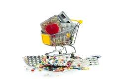 Het winkelen karretje met pillen, hart op witte achtergrond wordt geïsoleerd die Stock Afbeeldingen