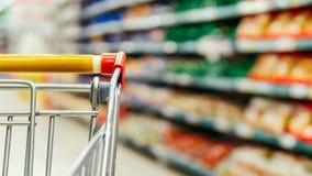 Het winkelen karretje in supermarktdoorgang, exemplaarruimte royalty-vrije stock foto