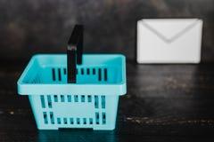 Het winkelen mand en e-mailenvelop naast het stock afbeeldingen