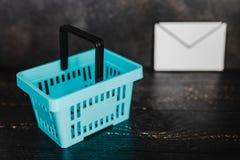 Het winkelen mand en e-mailenvelop naast het stock foto's