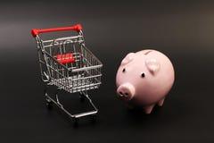 Het winkelen mand en roze spaarvarken op zwarte achtergrond Royalty-vrije Stock Fotografie