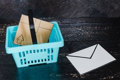 Het winkelen mand met pakket binnen en e-mailenvelop naast het royalty-vrije stock afbeeldingen