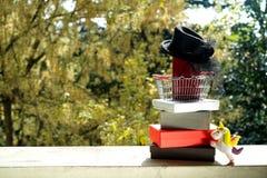 Het winkelen mand met rode beurs en kleine zwarte vrouwelijke hoed met v royalty-vrije stock foto