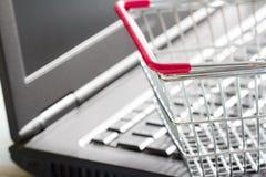 Het winkelen mand op laptop die online abstract concept kopen als achtergrond Stock Foto