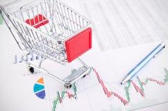 Het winkelen mandstuk speelgoed op bedrijfsdocumentenachtergrond Royalty-vrije Stock Foto