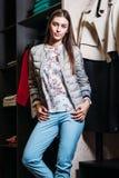 Het winkelen, manier, stijl, verkoop, het winkelen, zaken en mensen concepten mooie gelukkige jonge vrouw in kledingsopslag Zaken stock foto