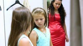 Het winkelen in montageruimte van grote opslag, mooi, ernstig meisje, probeert een jong geitje op nieuwe uitrustingen, kiest te k stock footage
