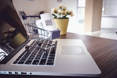 Het winkelen online concept, Minikarretje op toetsenbordlaptop Royalty-vrije Stock Afbeelding
