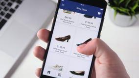 Het winkelen online het gebruiken smartphone app en het kiezen van schoenen stock footage
