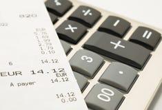 Het winkelen ontvangstbewijs op een calculator Stock Fotografie