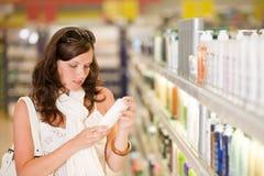 Het winkelen schoonheidsmiddelen - de shampoo van de vrouwenholding Stock Foto's