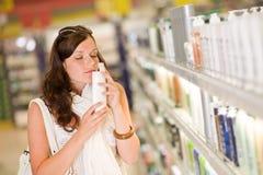 Het winkelen schoonheidsmiddelen - vrouwen ruikende shampoo stock afbeeldingen