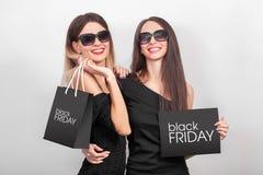 Het winkelen Twee vrouwen die zwarte zakken op lichte achtergrond in B houden Royalty-vrije Stock Afbeeldingen
