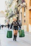 Het winkelen, verkoop Mooi jong blondemeisje met twee Groenboekpakketten stock foto's