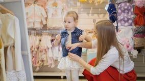 Het winkelen voor jonge geitjes - de dochter van de mammahulp om denimjasje omhoog dicht te knopen Royalty-vrije Stock Foto