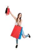 Het winkelen vrolijke jonge vrouwenholding gekleurde zakken over haar hoofd Stock Afbeeldingen