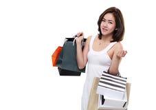 Het winkelen vrouw Aziatische gelukkige die het glimlachen holding het winkelen zakken op witte achtergrond worden geïsoleerd Stock Afbeelding
