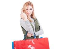 Het winkelen vrouwelijke holdingszakken en het wensen van goed geluk Royalty-vrije Stock Foto