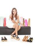 Het winkelen vrouwenzitting tussen het winkelen zakken en paren schoenen Stock Afbeelding