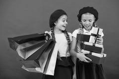 Het winkelen wordt pret met beste vrienden Kinderen tevreden door het winkelen rode achtergrond Geobsedeerd met het winkelen en stock fotografie