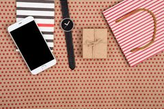 het winkelen zak, giftvakje, blocnote, horloge en slimme telefoon op ambachtdocument achtergrond in rode stippen stock afbeeldingen