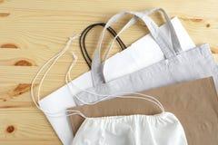 het winkelen zakken op houten achtergrond Katoenen en document zakken voor het vrije plastic winkelen royalty-vrije stock afbeeldingen