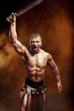 Het winnen gebaar die van gladiator zich in een rook in helm en met zwaard bevinden Royalty-vrije Stock Foto's