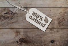 Het wit hangt het etiket van het markeringskarton met koord vastmaakte een tekst 100 percenten natuurlijk op rustieke houten lijs stock foto's