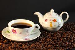Het wit met kleurrijke ontwerpen, ceramische koffiereeks, roosterde koffiebonen, donkere achtergrond Stock Afbeeldingen