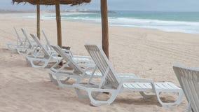 Het wit ontspant stoelen in strand dicht bij oceaan, Portugal stock videobeelden