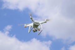 Het wit van vluchtquadrocopters tegen de blauwe hemel met wolken Stock Foto's