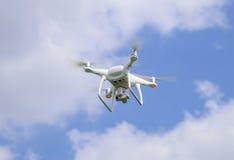 Het wit van vluchtquadrocopters tegen de blauwe hemel met wolken Royalty-vrije Stock Foto's