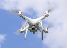 Het wit van vluchtquadrocopters tegen de blauwe hemel met wolken Stock Afbeelding