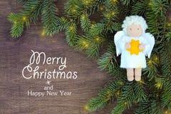 Het wit voelde Kerstmisengel met gele ster in handen aan verse natuurlijke takken van Kerstboomsparren op houten achtergrond vector illustratie