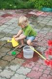 Het wit weinig blootvoets meisje die met water spelen kan royalty-vrije stock foto