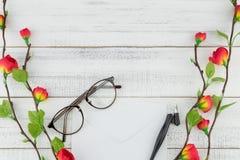 Het wit wikkelt, schuine die pen en oogglazen met valse rode bloemen wordt verfraaid Royalty-vrije Stock Foto's