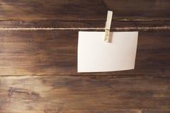 Het witte blad van document hangen op wasknijper, plaats voor tekst, op een achtergrond van oude houten Stock Foto