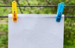 Het witte blad van document hangen op wasknijpers stock afbeeldingen